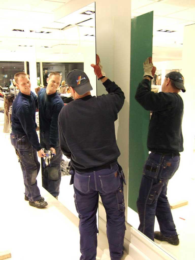 Leende montörer installerar en ny spegel