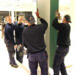 Glada arbetare sätter upp speglar